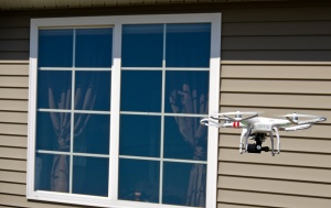 drone hovering near house window
